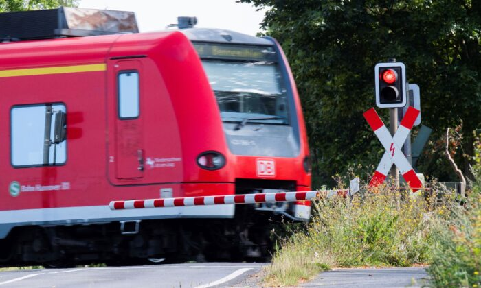 A Deutsche Bahn (DB) commuter train passes a level crossing with a red light in Roessing, Germany, on Aug. 11, 2021. (Julian Stratenschulte/dpa via AP)