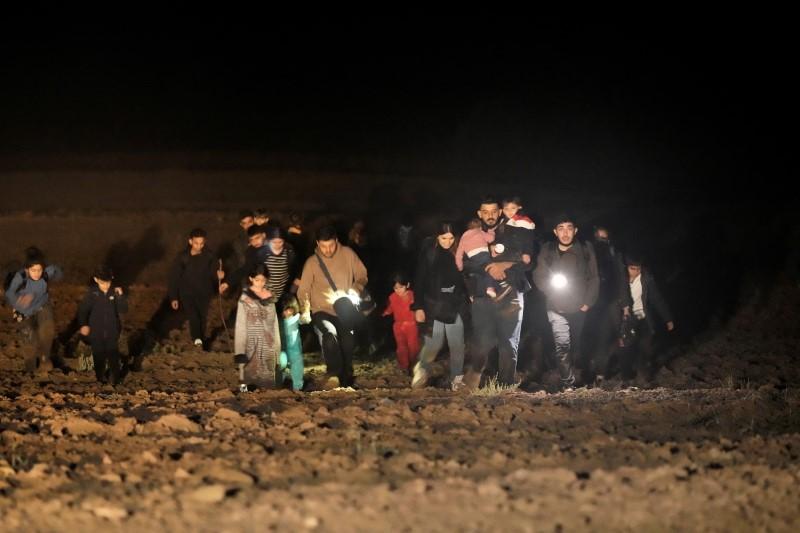 Detained migrants walk next to the Belarus-Latvia border near Vorzova