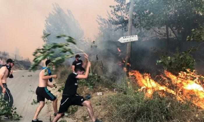 People attempt to put out a fire in the mountainous Tizi Ouzou province, east of Algiers, Algeria, on Aug. 10, 2021. (Abdelaziz Boumzar/Reuters)