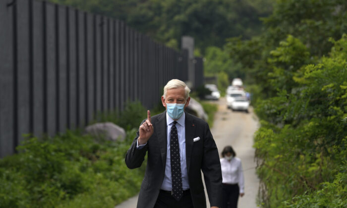 Dominic Barton, Canada Ambassador to China, wearing a face mask gestures after meeting with Canadian Michael Spavor at a detention center in Dandong, China, Aug. 11, 2021. A Chinese court has sentenced Spavor to 11 years on spying charges in case linked to Huawei. (AP Photo/Ng Han Guan)