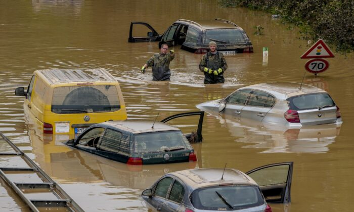 People check for victims in flooded cars on a road in Erftstadt, Germany, on July 17, 2021. (Michael Probst/AP Photo)