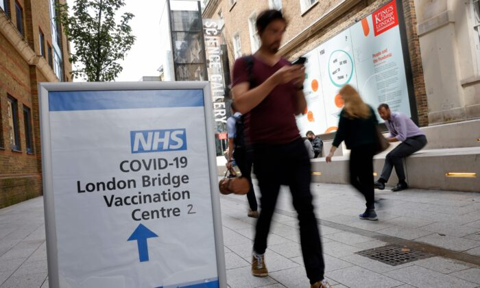 People pass signs indicating the entrance to the London Bridge Vaccination Centre in London on Aug. 9, 2021. (Tolga Akmen/AFP via Getty Images)