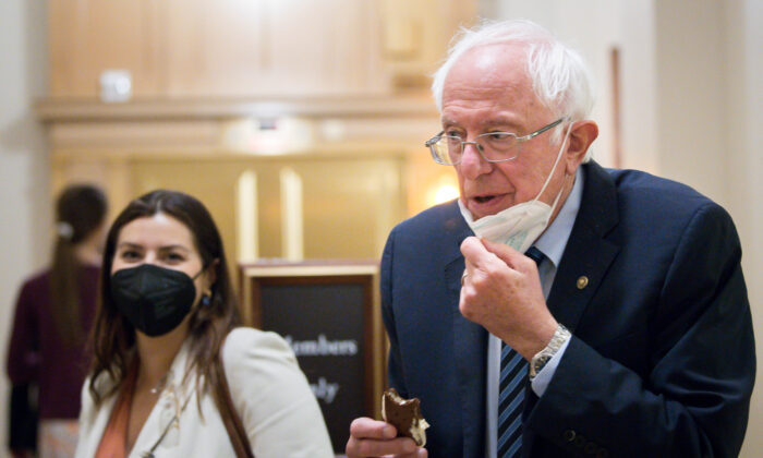 Sen. Bernie Sanders (I-Vt.) lowers his mask to take a bite of an ice cream sandwich while taking a break from the Senate floor budget resolution proceedings in Washington on Aug, 10, 2021. (Liz Lynch/Getty Images)
