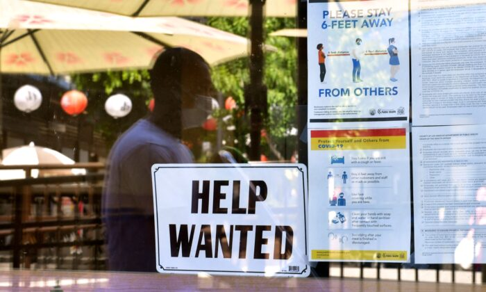 A 'Help Wanted' sign is posted beside Coronavirus safety guidelines in front of a restaurant in Los Angeles on May 28, 2021. (Frederic J. Brown/AFP via Getty Images)