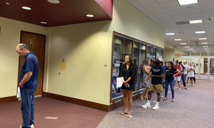 Speakers waited in a group of ten outside the board room while other speakers waited outdoors or in their cars during the Loudoun County Public School Board meeting, Va., on Aug. 10, 2021. (Terri Wu/The Epoch Times)