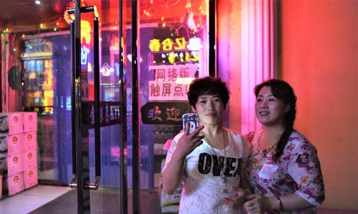 Two women outside a karaoke bar in Hunchun, in China's northeast Jilin province, on June 24, 2015. (Greg Baker/AFP via Getty Images)
