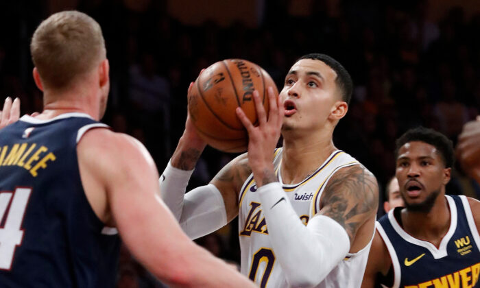 The Los Angeles Lakers' Kyle Kuzma goes to the basket against the Denver Nuggets' Mason Plumlee, left, at Staples Center in Los Angeles on Dec. 22, 2019. (Luis Sinco/Los Angeles Times/TNS)