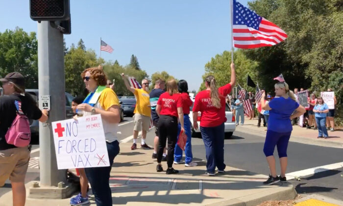 Protesters with flags, banners, and signs stand along the sidewalk on Eureka Road in Roseville, Calif., on Aug. 9, 2021. (Courtesy of Rui Ren)