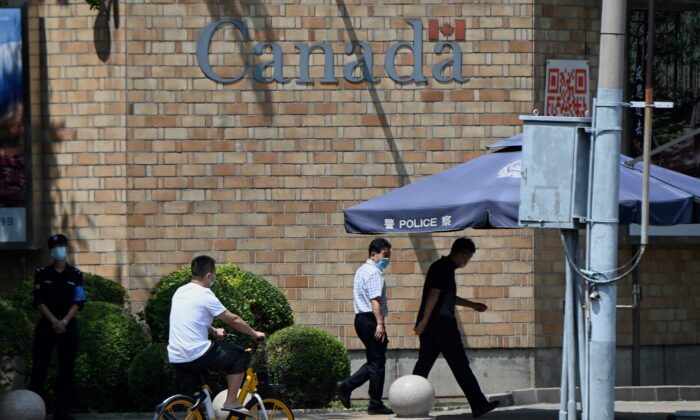 People walk past the Canadian Embassy as a Chinese court upheld the death sentence passed on Canadian citizen Robert Lloyd Schellenberg for drug smuggling in Beijing on Aug. 10, 2021. (Noel Celis/AFP via Getty Images)