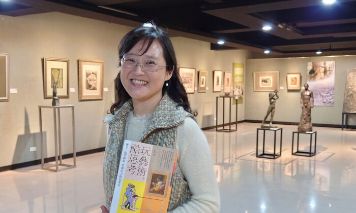 """Taiwanese author Iris Chiang holds her book """"Play with Art"""" at the saloon featuring Taiwanese artist YUYU Yang's work in Taipei, Taiwan, on March 23, 2021. (Chiang Ying-ying/AP Photo)"""