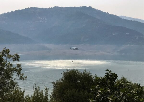 A helicopter collects water to extinguish a wildfire in Tizi Ouzou