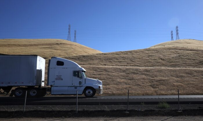 A truck drives by hills covered in dry grass along Highway 5 in Los Banos, Calif., on May 25, 2021. (Justin Sullivan/Getty Images)