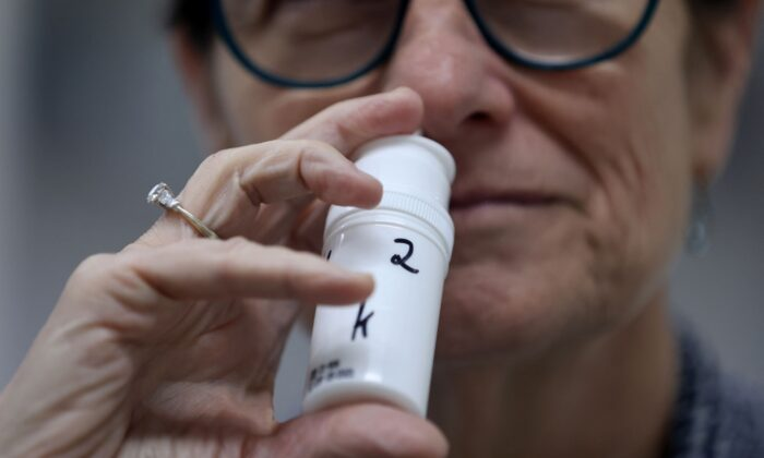 A technician displays a sample of an anti-viral nose spray on April 7, 2021. (Emmanuel Dunand/AFP via Getty Images)