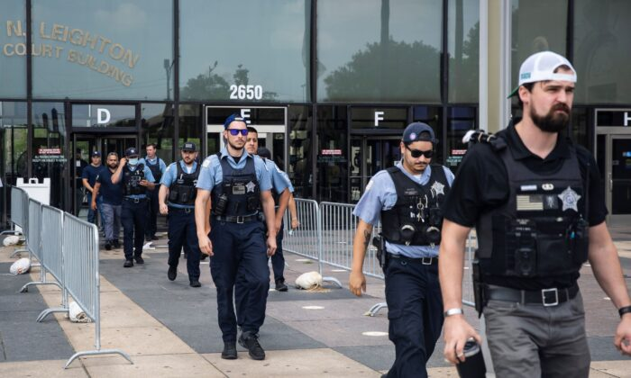 Dozens of Chicago police officers and personnel walk out of the Leighton Criminal Courthouse after attending the bond hearings for two brothers charged in connection with the fatal shooting of Officer Ella French, Tuesday, Aug. 10, 2021, in Chicago. French was fatally shot and her partner was critically wounded in West Englewood while in the line of duty Saturday night. (Ashlee Rezin/Chicago Sun-Times via AP)
