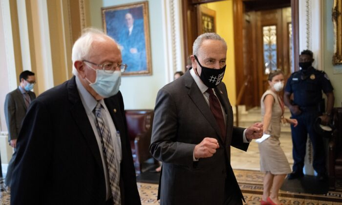 Sen. Bernie Sanders (L) (I-Vt.) walks with Senate Majority Leader Chuck Schumer (D-N.Y.) after meeting on a $3.5 trillion budged in Washington on Aug. 9, 2021. (Win McNamee/Getty Images)