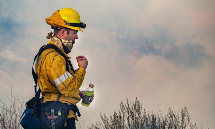 OCFA firefighter takes a sip of Gatorade during the Bond Fire on Dec. 5, 2020. (John Fredricks/The Epoch Times)