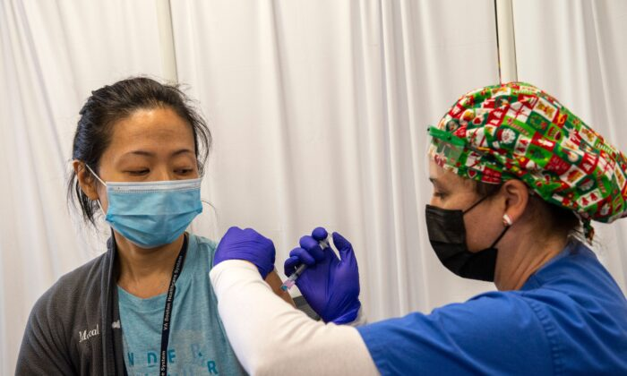 Nurse and Army veteran Renee Langone administers a Moderna COVID-19 vaccine to US Air Force (active duty reservist) Doctor Pei-Chun McGregor at the West Roxbury VA Medical Center in Boston, Mass. on Dec. 23, 2020. (Joseph Prezioso/AFP via Getty Images)