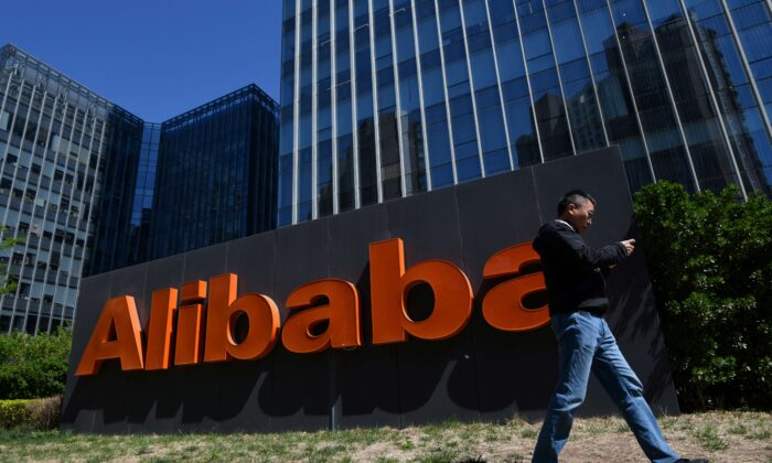 A man walks past an Alibaba sign outside the company's office in Beijing on April 13, 2021. (Greg Baker/AFP via Getty Images)