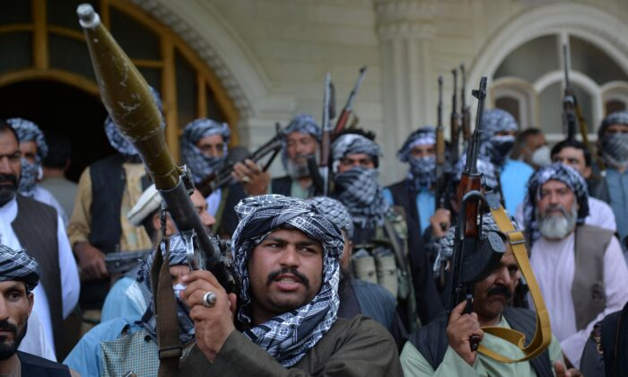 Afghan militia gather with their weapons to support Afghanistan security forces against the Taliban, in Afghan warlord and former Mujahideen leader Ismail Khan's house in Herat, Afghanistan on July 9, 2021. (Hoshang Hashimi/AFP via Getty Images)