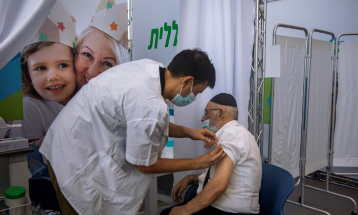A man receives a third Pfizer-BioNTech COVID-19 vaccine from medical staff member at a coronavirus vaccination center in Tel Aviv, Israel, on Aug. 10, 2021. (Oded Balilty/AP Photo)