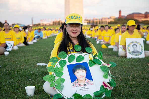 Yang Chunhua holds a wreath commemorating her sister, Yang Chunling, who passed away in 2014 as a result of Beijing's persecution of Falun Gong, during an event in Washington on July 18, 2019. (The Epoch Times)