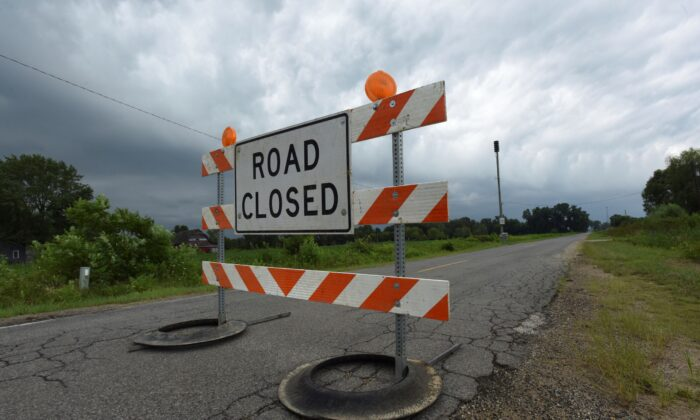 Recent heavy rains have closed area roads in Southwest Michigan including Holden Road at Shawnee Road in Bridgman, Mich., on Aug. 11, 2021. (Don Campbell/The Herald-Palladium via AP)