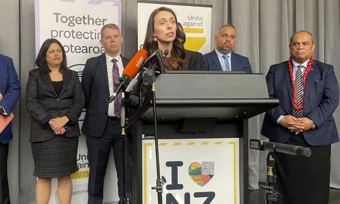 Flanked by lawmakers, New Zealand Prime Minister Jacinda Ardern delivers a speech in Wellington, New Zealand, on Aug. 12, 2021. (Nick Perry/AP Photo)
