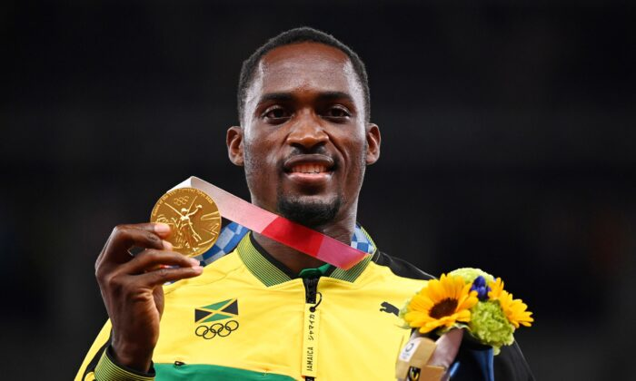 Gold medallist, Hansle Parchment of Jamaica poses on the podium at the men's 110 meter hurdles Tokyo 2020 Olympics medal ceremony in Tokyo, Japan, on Aug. 5, 2021. (Dylan Martinez/File Photo/Reuters)