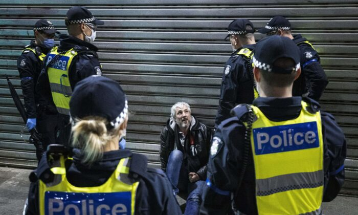 A man is detained and questioned by Police during a proposed anti-lockdown protest in Melbourne, Australia, on Aug. 11, 2021. (AAP Image/Daniel Pockett)