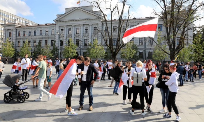 """Demonstrators wear Belarusian flags during a rally called """"We won't forget, We won't forgive!"""" in front of the Museum of Occupations and Freedom Fights in Vilnius, Lithuania, on Aug. 9, 2021, one year after a disputed election and protests that erupted thereafter in Belarus.(PETRAS MALUKAS/AFP via Getty Images)"""