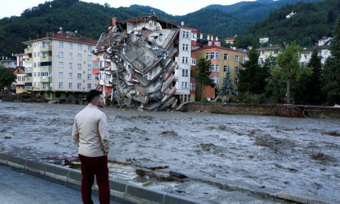 A man looks on as flood waters sweep by in Bozkurt town of Kastamonu province of Turkey, on Aug. 12, 2021. (IHA via AP)