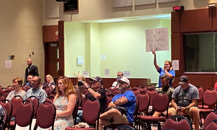 A woman holds a sign as board member Jeff Morse speaks at the Loudoun County Public Schools board meeting in Virginia on Aug. 11, 2021. (Terri Wu/The Epoch Times)