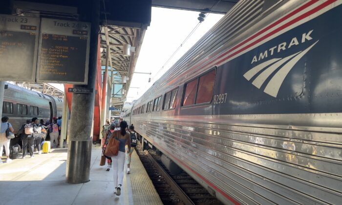 Passengers walk along an Amtrak train on a track at Union station in Washington on July 18, 2021. (Daniel Slim/AFP via Getty Images)
