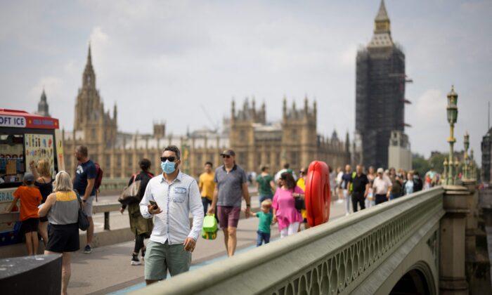 Pedestrians, cross Westminster Bridge in central London on July 26, 2021. (Tolga Akmen / AFP via Getty Images)