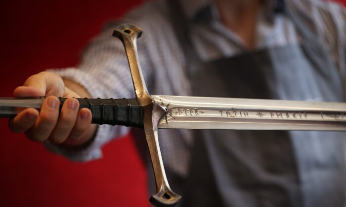 A Bonhams employee holds 'Anduril' a prop sword belonging to Aragorn, hero of 'The Lord of the Rings' movie trilogy in London, England, on July 31, 2014. (Peter Macdiarmid/Getty Images)