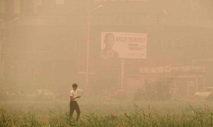 A boy walks through smoke from a forest fire that covers Yakutsk, the capital of the republic of Sakha also known as Yakutia, Russia Far East, Russia, on Aug. 12, 2021. (Ivan Nikiforov/AP Photo)