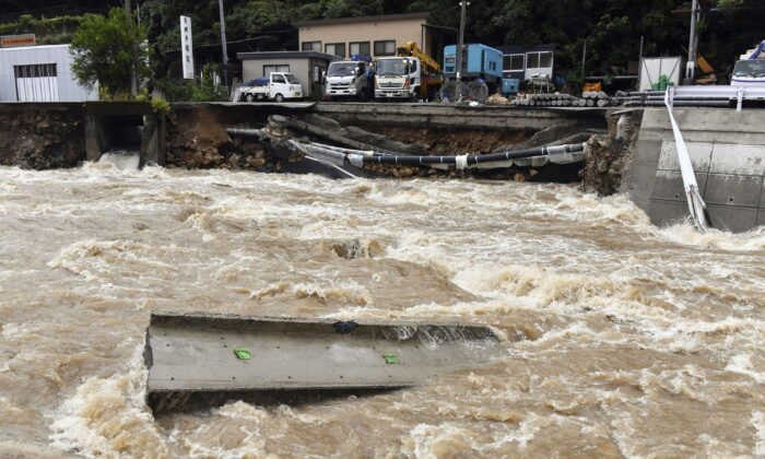 A road is damaged by the swollen Suzuhari river caused by a heavy rain in Hiroshima, western Japan, on Aug. 13, 2021. (Kyodo/via Reuters)