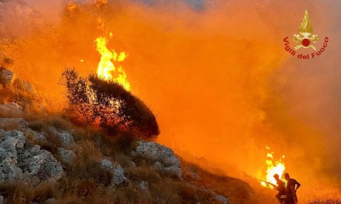 Firefighters battle wildfires in the beach village of Porto Badisco near Otranto in the southern region of Puglia, Italy, on Aug. 13, 2021. (Vigili del Fuoco/Handout via Reuters)