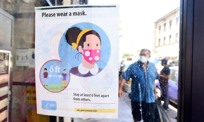 A storefront sign reminds people to wear a facemask in Los Angeles, California, on July 19, 2021. (Frederick J.Brown /AFP via Getty Images)