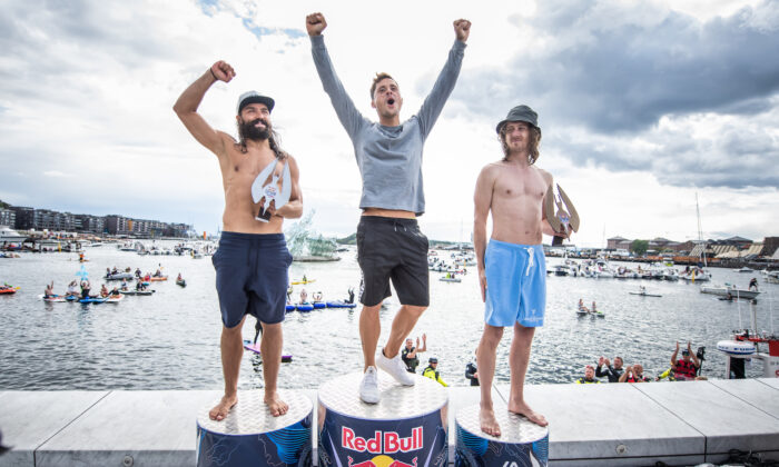 (L–R) Catalin Preda of Romania, Constantin Popovici of Romania, and Gary Hunt of France celebrate on the podium at the Oslo Opera House after the final competition day of the Red Bull Cliff Diving Exhibition in Oslo, Norway, on Aug. 13, 2021. (Romina Amato/Red Bull Content Pool)