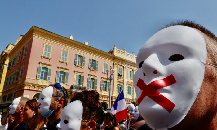 Protesters march against the coronavirus disease (COVID-19) vaccination and the use of health passes to restaurants, bars, trains, and planes in Nice, France, on Aug. 14, 2021. (Eric Gaillard/Reuters)
