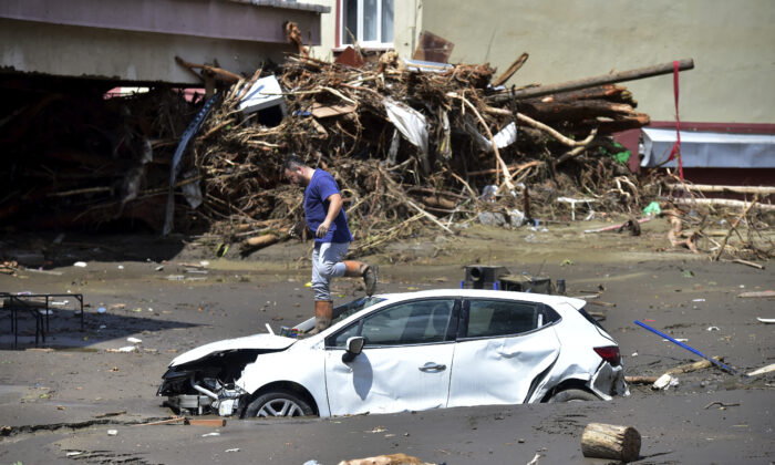 A man checks his car buried in the mud after floods and mudslides killed about three dozens of people, in Bozkurt town of Kastamonu province, Turkey, on Aug. 13, 2021. (AP Photo)
