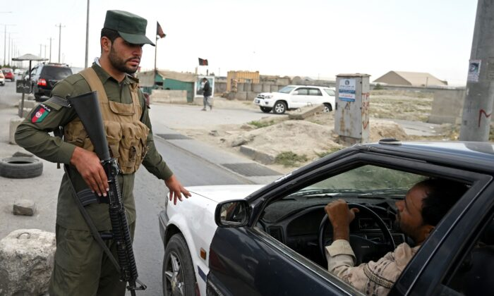 An Afghan policeman speaks to a commuter in car at a checkpoint along the road in Kabul, Afghanistan on Aug. 14, 2021. (Wakil Kohsar/AFP via Getty Images)