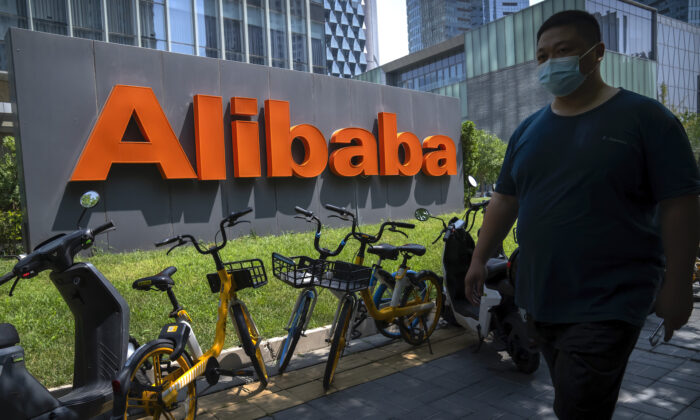 A man wearing a face mask walks past the offices of Chinese e-commerce firm Alibaba in Beijing, on Aug. 10, 2021. (AP Photo/Mark Schiefelbein)