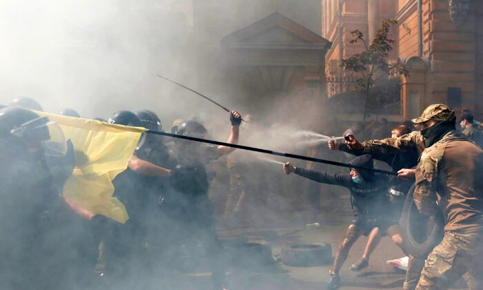 Demonstrators clash with police officers during a protest by activists of the National Corps political party in front of the presidential office building in Kyiv, Ukraine, on Aug. 14, 2021. (Serhii Nuzhnenko/Reuters)
