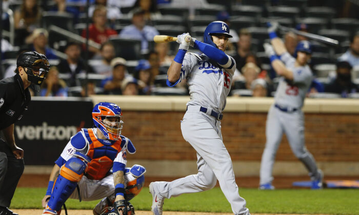 Los Angeles Dodgers center fielder Cody Bellinger (35) follows through on a double against the New York Mets  during the tenth inning of a baseball game in New York on Aug. 14, 2021.  (AP Photo/Noah K. Murray)