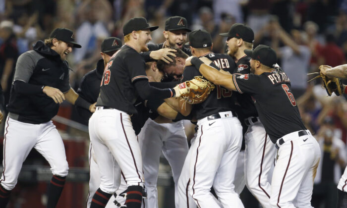 Starting pitcher Tyler Gilbert #49 of the Arizona Diamondbacks is surrounded by teammates as they celebrate following Gilbert's no hitter against the San Diego Padres during the MLB game at Chase Field in Phoenix, Ariz., on Aug. 14, 2021. (Ralph Freso/Getty Images)