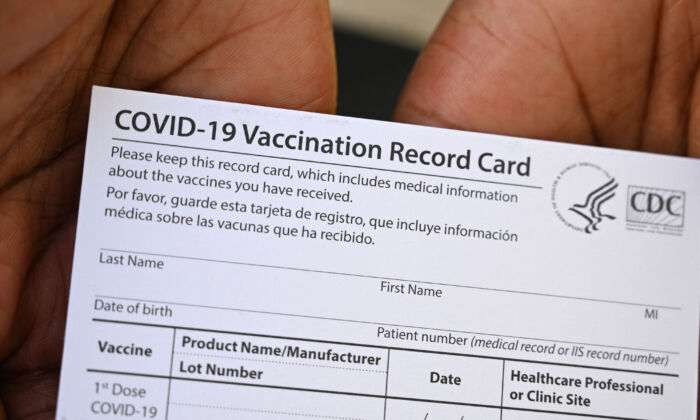 A health care worker displays a COVID-19 Vaccination Record Card during a vaccine and health clinic at QueensCare Health Center in Los Angeles on Aug. 11, 2021. (Robyn Beck/AFP via Getty Images)