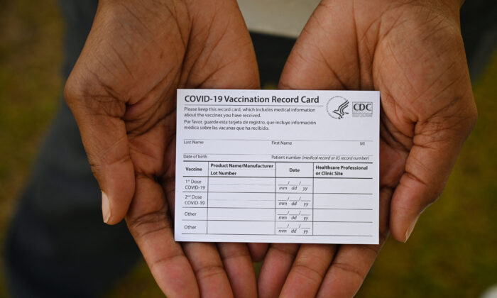 A health care worker displays a COVID-19 Vaccination Record Card during a vaccine and health clinic at QueensCare Health Center in a predominantly Latino neighborhood in Los Angeles, Calif., on Aug. 11, 2021. (Robyn Beck/AFP via Getty Images)