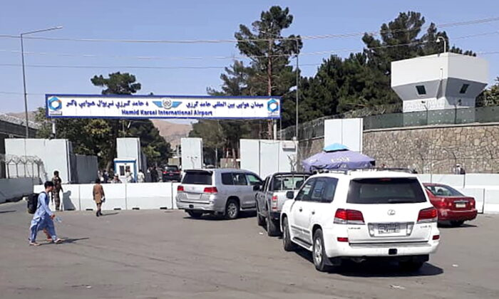 Afghan police check the cars at the entrance gate of Hamid Karzai International Airport in Kabul, Afghanistan, on Aug. 15, 2021. (Stringer/Reuters)